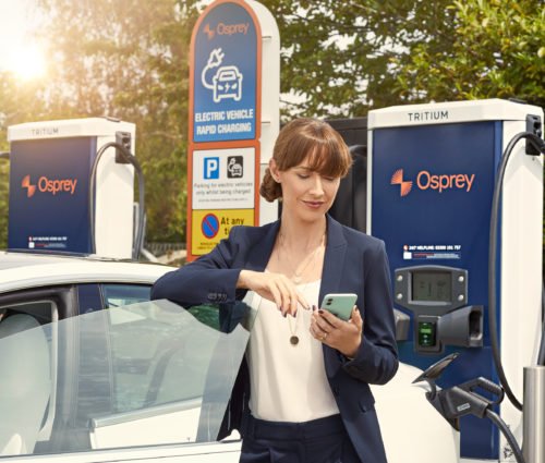 Woman using phone at EV chargepoint