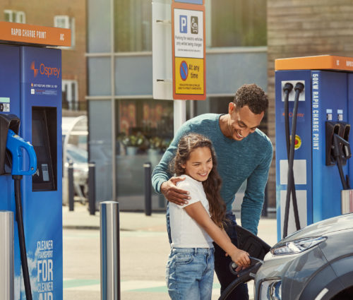 A father and daughter charging their electric vehicle at an Osprey chargepoint