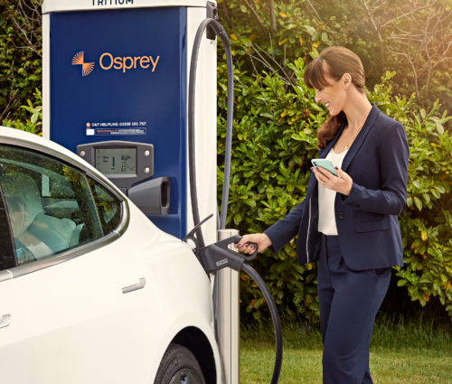 Woman charges her Tesla at an Osprey chargepoint