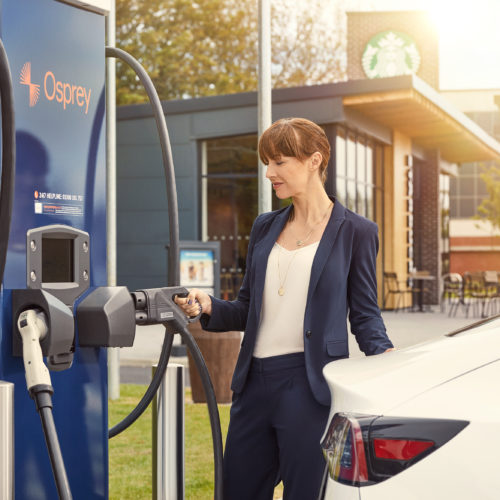 A woman charges her car by a Starbucks